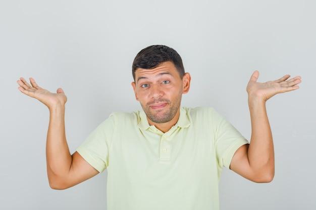 Mann im gelben t-shirt, das hilflose geste mit arm und händen zeigt und unentschlossen schaut