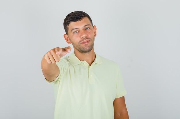 Mann im gelben t-shirt zeigt finger auf kamera und schaut entscheidend