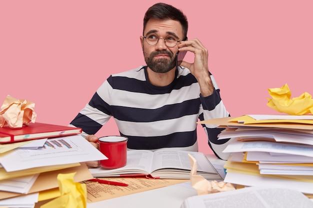 Mann im gestreiften hemd, das am schreibtisch mit dokumenten sitzt