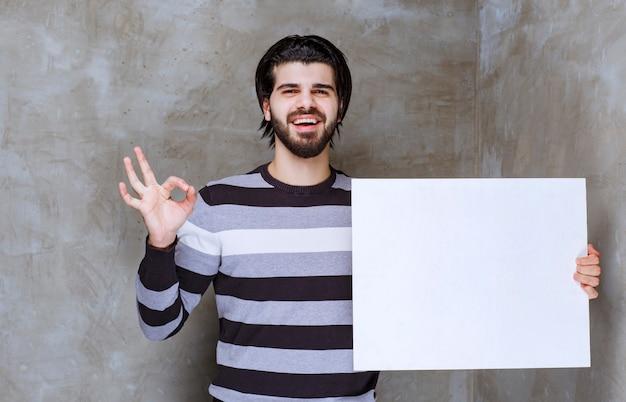 Mann im gestreiften hemd, das ein weißes quadratisches papier hält und friedens- und freundschaftszeichen zeigt