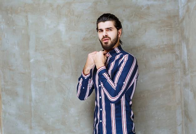 Mann im gestreiften hemd, das ihre fäuste zeigt und sich stark fühlt.