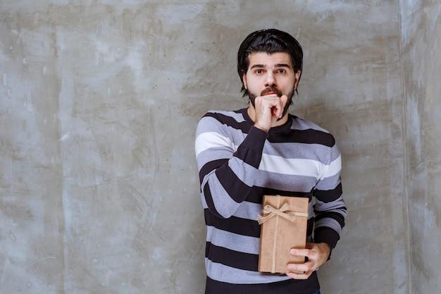 Mann im gestreiften hemd hält eine geschenkbox aus karton und sieht verwirrt und verängstigt aus