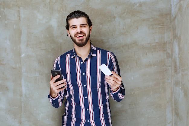 Mann im gestreiften hemd hält eine visitenkarte und sein smartphone beim lächeln