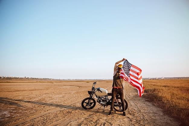 Mann im goldenen helm, der amerikanische flagge an der wüste mit motorrad auf dem hintergrund hält
