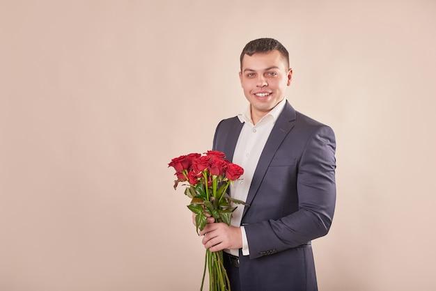 Mann im grauen anzug mit roten rosen