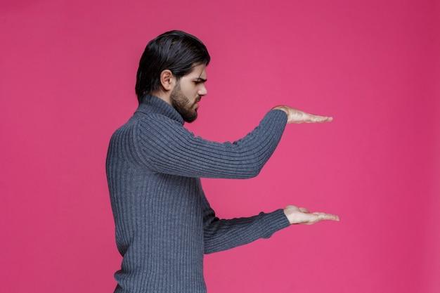 Mann im grauen hemd, das höhe einer sache mit händen zeigt.