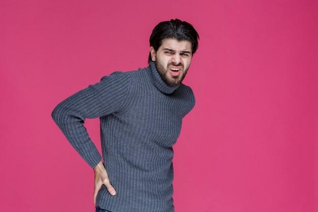 Mann im grauen hemd hält hände in seiner taille, als hätte er rückenschmerzen.