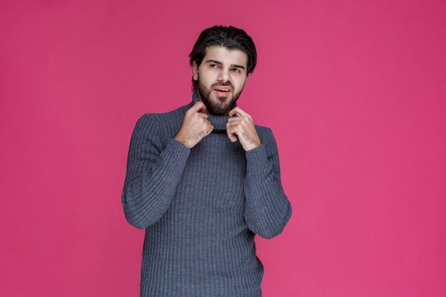 Mann im grauen hemd sieht selbstbewusst aus.