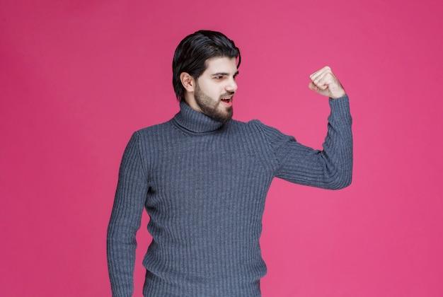 Mann im grauen pullover demonstriert seine armmuskeln.