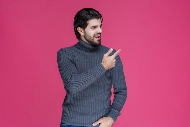 Mann im grauen pullover, der etwas zeigt oder jemanden mit dem zeigefinger vorstellt.