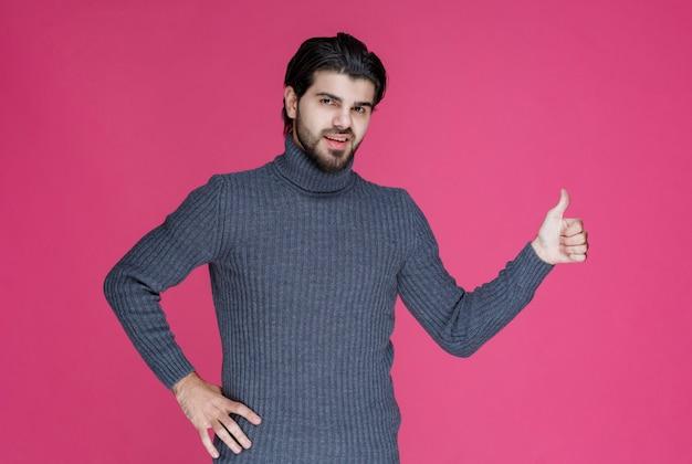 Mann im grauen pullover, der positives und gutes handzeichen macht.
