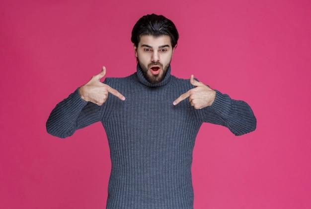 Mann im grauen pullover, der sich mit dem zeigefinger zeigt.