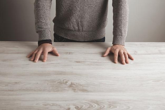 Mann im grauen pullover hält hände auf leerem weißem holztisch, lokalisiert auf einfacher wand