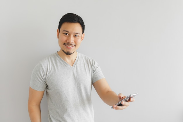 Mann im grauen t-shirt benutzt den smartphone.