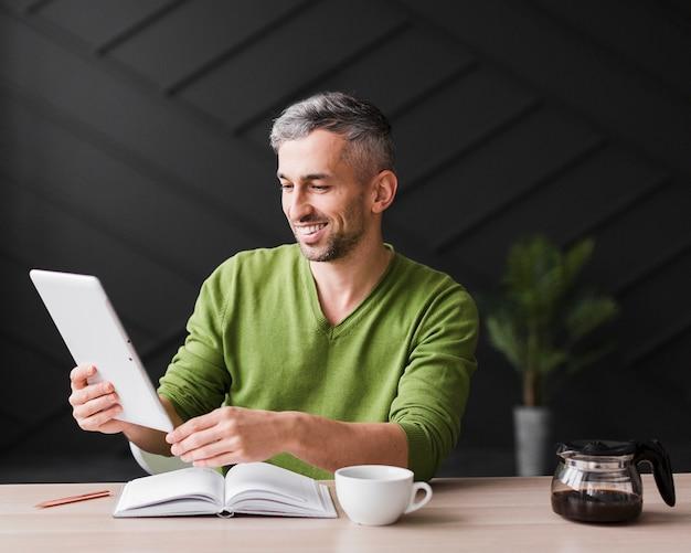 Mann im grünen hemd, das eine digitale tablette hält