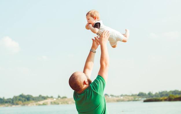 Mann im grünen hemd wirft sein kind auf
