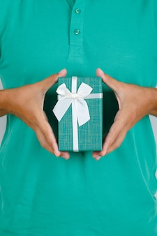 Mann im grünen t-shirt, das geschenkbox, vorderansicht hält.