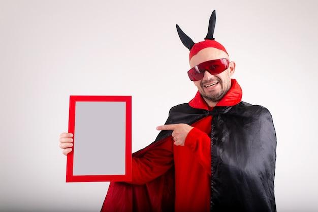 Mann im halloween-kostüm, der leeres typenschild demonstriert