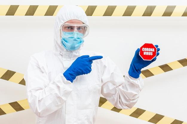 Mann im hazmat-anzug mit coronavirus-stoppschild