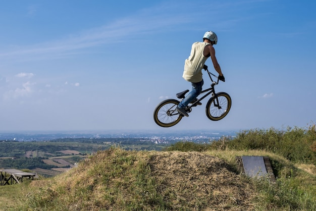 Mann im helm auf einem fahrrad, das auf einem hügel gegen den blauen himmel springt und fliegt