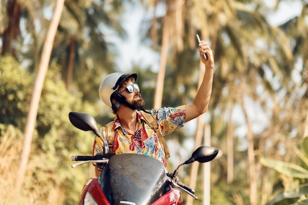 Mann im helm sitzt auf motorrad und benutzt handy