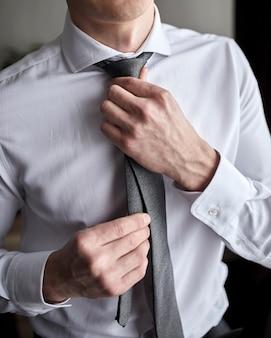Mann im hemd verkleidet sich und passt die krawatte am hals zu hause an
