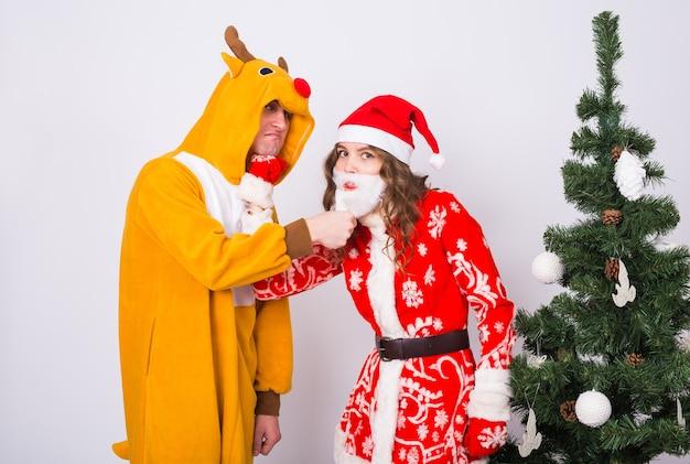 Mann im hirschkostüm und frau im weihnachtsmannkostüm nahe weihnachtsbaum