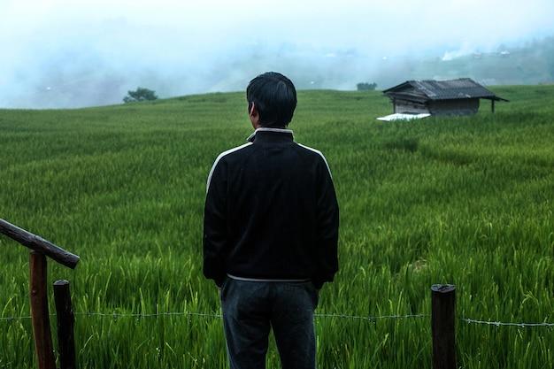 Mann im holz terassenförmig angelegt mit reisfeldern und bergblick in bewölkten himmel