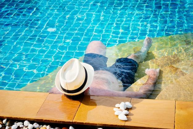 Mann im hut, der auf dem swimmingpool sich entspannt