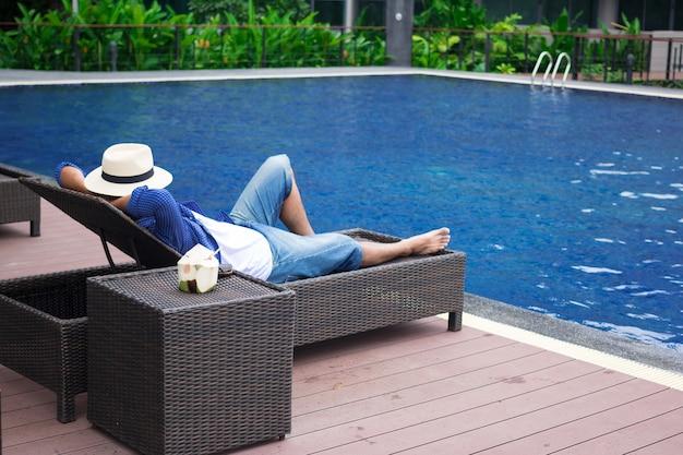 Mann im hut, der auf liegestühlen mit sonnenaufgang morgens ein sonnenbad nimmt