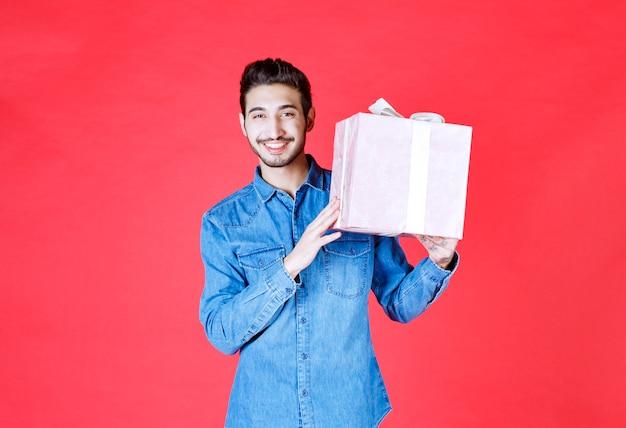 Mann im jeanshemd, das eine lila geschenkbox hält, die mit weißem band gebunden ist.