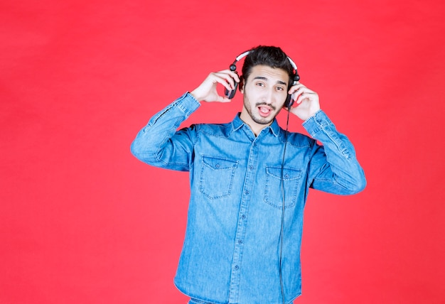 Mann im jeanshemd, das kopfhörer trägt und die neuen tracks hört.