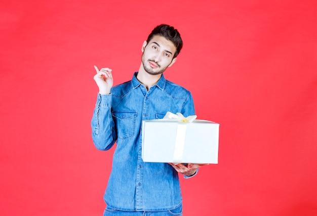 Mann im jeanshemd, das silberne geschenkbox hält und auf irgendwo zeigt.