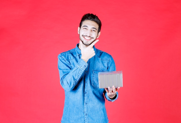 Mann im jeanshemd, das silberne geschenkbox hält.