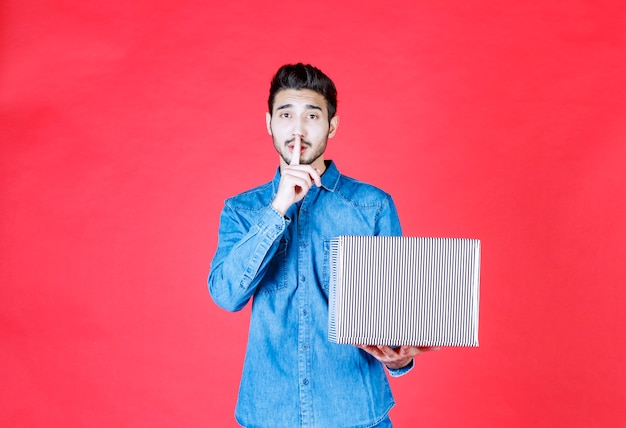 Mann im jeanshemd hält silberne geschenkbox und bittet um stille.