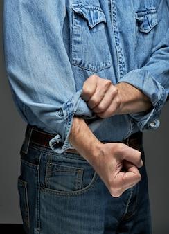 Mann im jeanshemd krempelt die ärmel hoch