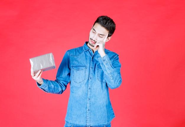 Mann im jeanshemd mit silberner geschenkbox und sieht verwirrt und unerwartet aus.