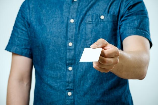 Mann im jeanshemd zeigt leere weiße visitenkarte für sie zu geben