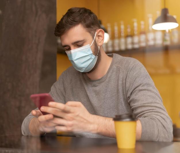 Mann im kaffeehaus, der eine medizinische maske trägt