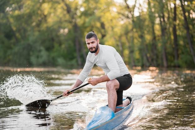 Mann im kanu, der vollen schuss paddelt