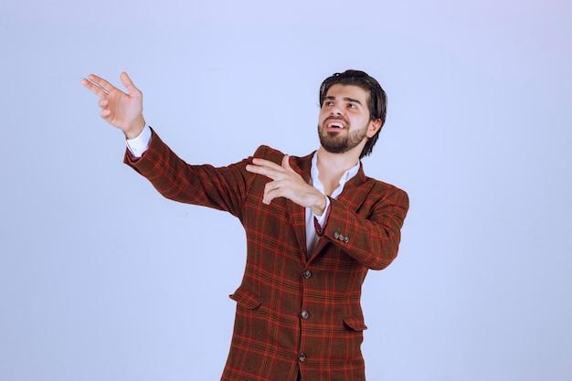 Mann im karierten blazer, der eine rede in der szene hält und etwas oben präsentiert.