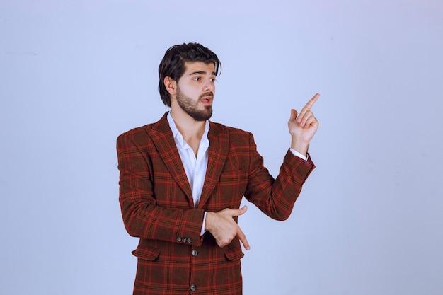 Mann im karierten blazer zeigt auf etwas rechts und spricht darüber.