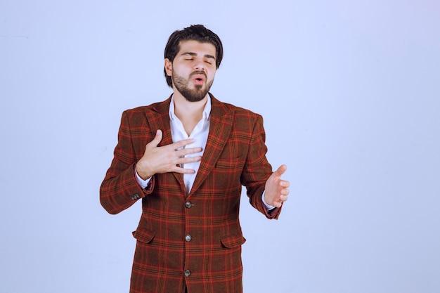 Mann im karierten blazer zeigt und erhält lob für sich.