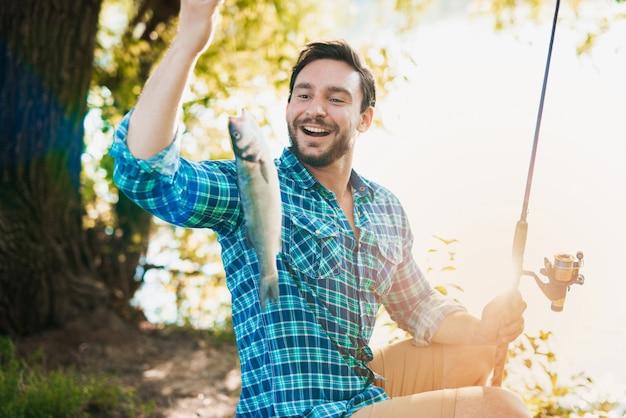 Mann im karierten hemd, das auf fluss im sommer fischt.