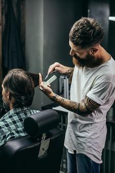 Mann im karierten hemd, das im friseursalon und im professionellen tätowierten friseur sitzt