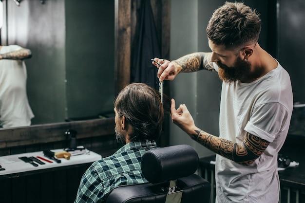 Mann im karierten hemd sitzt vor dem spiegel und erfahrener friseur