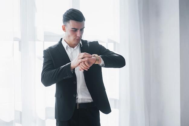Mann im klassischen anzug überprüft die zeit auf seinen goldenen luxusuhren.