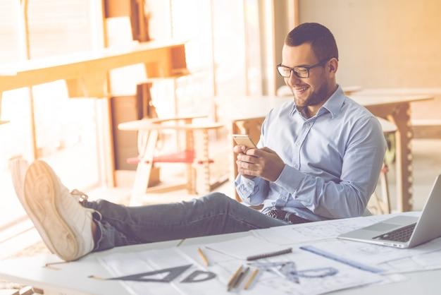 Mann im klassischen hemd und in den brillen benutzt einen smartphone