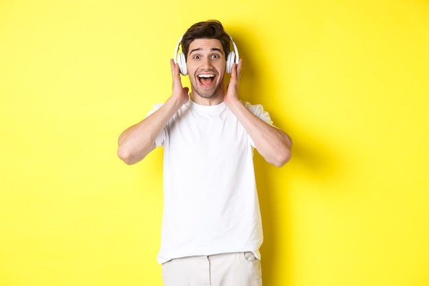 Mann im kopfhörer, der überrascht und glücklich schaut, fantastisches lied hört und über gelber wand steht