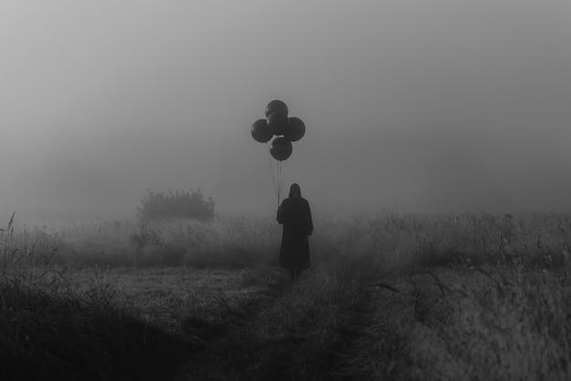 Mann im kostüm eines schrecklichen monsters in einem kap mit einer kapuze steht im nebel auf einem feld